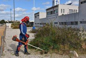 Un trabajador arregla los setos junto al estadio de atletismo