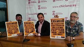 El delegado de Fiestas y los representantes de la Peña Hombres del Campo muestran el cartel anunciador del acto de hoy