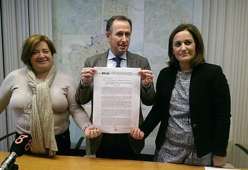 El alcalde junto a Cándida Verdier y Ana González muestran la publicación del BOJA