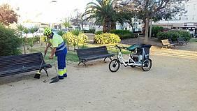 Un trabajador del servicio de limpieza realizando su trabajo junto al triciclo