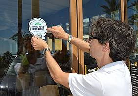 Un comerciante instala un cartel informativo sobre reciclaje en la puerta de su establecimiento