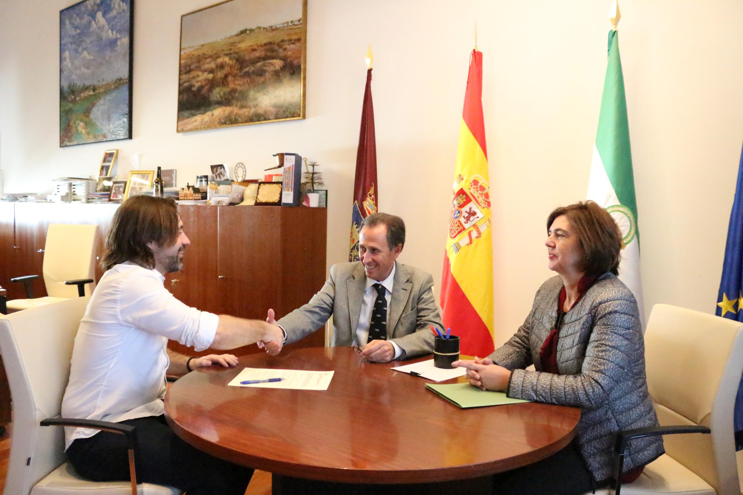 El alcalde y el representante de Pro Derechos Humanos se dan la mano durante el acto de firma de convenio, ante la presencia de la delegada municipal de Cooperación Internacional