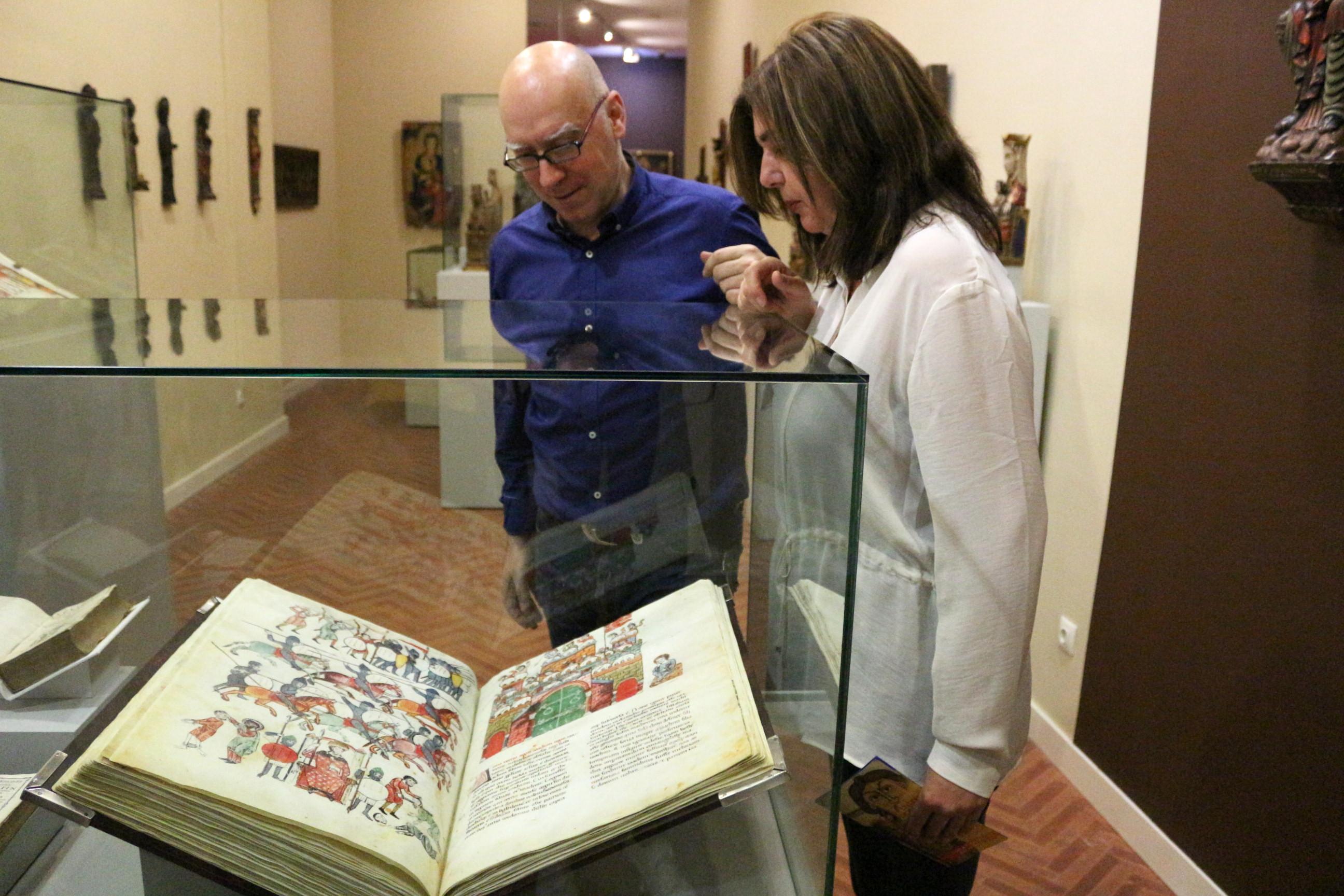 Pepa Vela y Jesús Romero observan un libro de la exposición